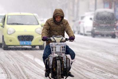 """资料图:2月19日,新一轮强降雪天气再度""""光临""""新疆乌鲁木齐市。 中新社记者 刘新 摄"""