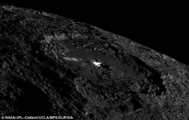 """谷神星上有一处神秘的撞击坑,其中有一些极为明亮的物质。科学家认为,这里或许曾是冰火山的""""喷发点""""。在近期一项研究中,科学家发现谷神星上的这些亮斑只有四百万年历史,比它们所处的撞击坑晚形成三千万年。"""