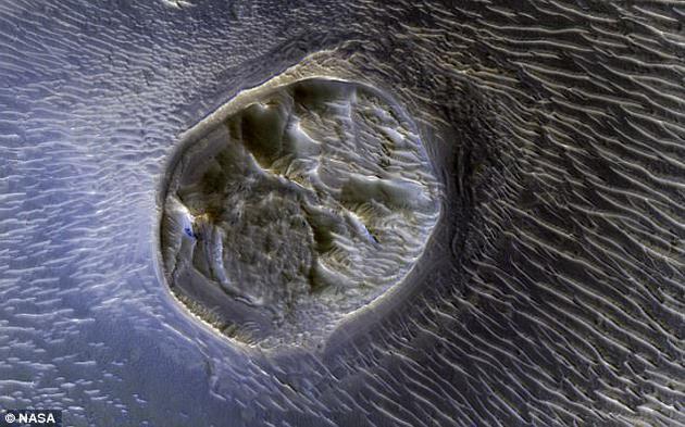 """照片上出现一处""""蜂窝""""状的迷宫地形。外星人搜寻爱好者声称,这是火星上一个神秘的外星人城市。不过,科学家认为,这可能是一种沉积层地形,经侵蚀风化逐渐裸露出地面而形成的奇特造型。"""