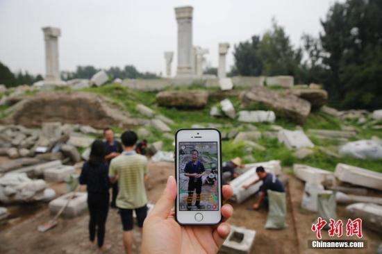 资料图 民众使用手机直播 中新社发 钟欣 摄