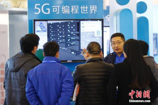 """资料图 参观者在""""互联网之光""""博览会上听取参展商介绍""""5G可编程世界""""。 中新社记者 盛佳鹏 摄"""