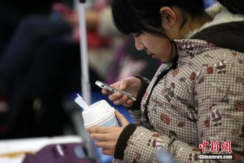 """铁路青岛站候车室内,玩手机的""""低头族""""随处可见。中新社发 徐崇德 摄"""
