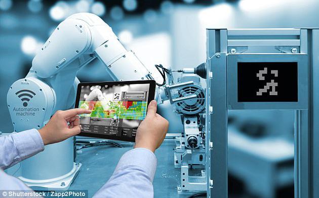 图为工作人员正手持一台增强现实显示屏,无线操控一家智能工厂中的机器臂。