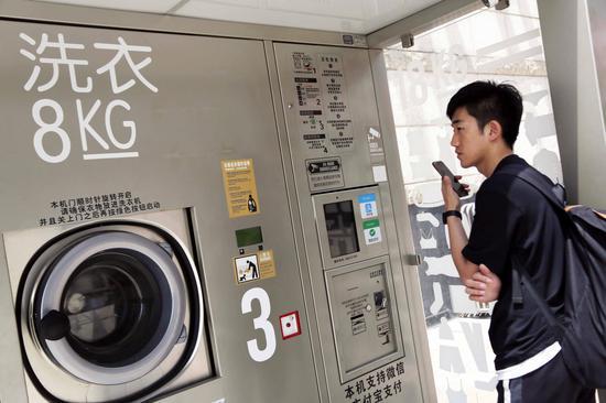 市民对共享洗衣机持有观望态度,在记者采访的半小时内,商场内人来人往,但并没有人使用该机器。