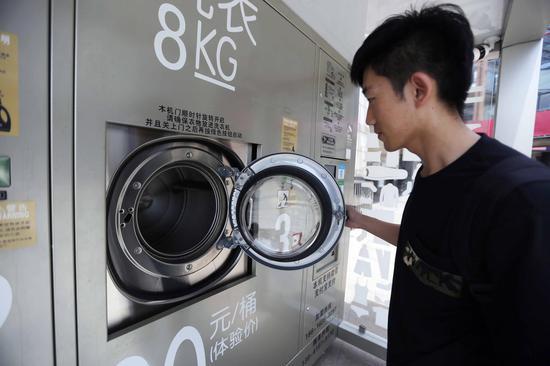 市民打开洗衣机门,查看滚筒内部。