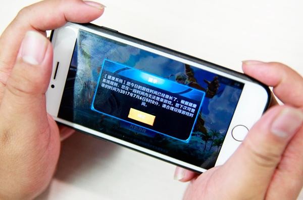 2017年7月5日,西安一名市民在玩《王者荣耀》。为了限制未成年人玩游戏的时间,《王者荣耀》启动史上最严未成年人防沉迷系统,到时间直接终止。