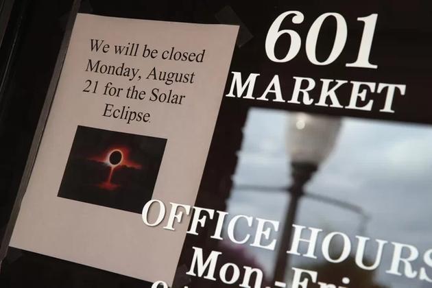 图中是美国伊利诺斯州梅特罗波利斯市一处商业窗口张贴的广告,他们将于8月21日全日食期间停止营业。