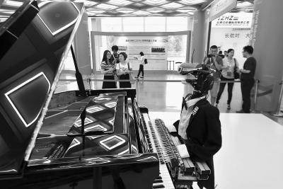 图为一名会弹钢琴的机器人西装革履、姿态优雅坐在钢琴前,很有艺术家风范。本报记者 和冠欣摄
