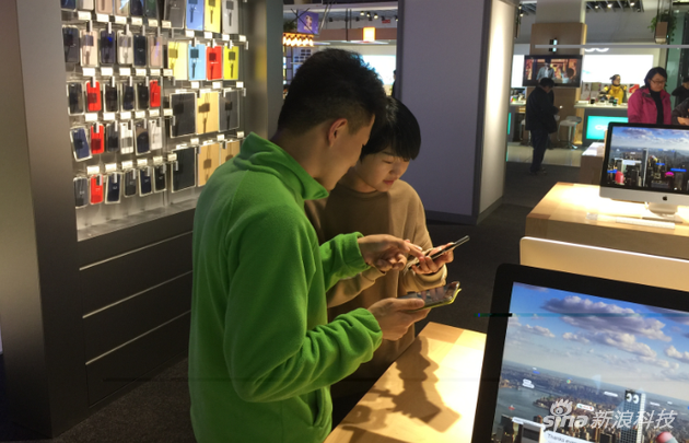 图:顾客正在苏宁门店内接受苹果产品设置服务的帮助