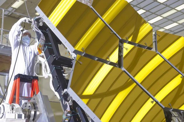 2011年,一名工程师正在美国宇航局马歇尔空间飞行中心对即将接受超低温测试的詹姆斯·韦伯空间望远镜巨大的镜面进行检查