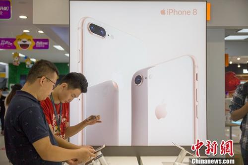 9月22日,山西太原,工作人员正在给民众介绍iPhone8手机新功能。当日,苹果最新手机iPhone8/8 Plus全球同步开售。中新社记者 张云 摄