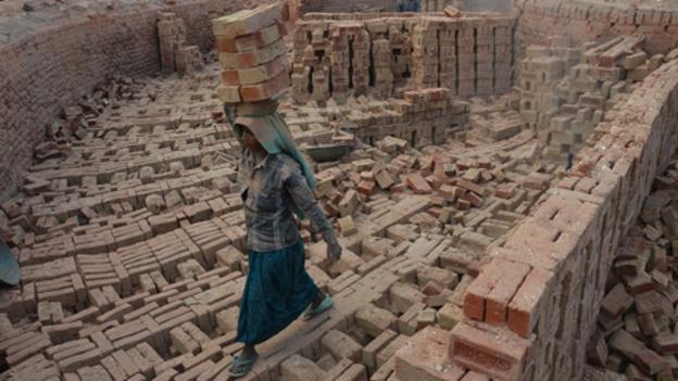 图中是一位印度妇女在印度那加兰邦一处砖窑厂搬砖。