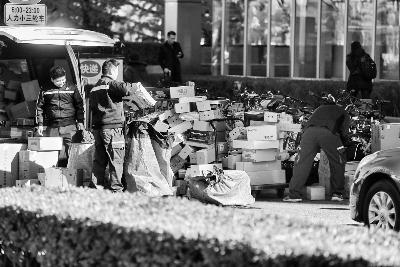 ▲在西城区闹市口大街,快递员正在路边整理、搬运快递包裹摄/记者 柴程