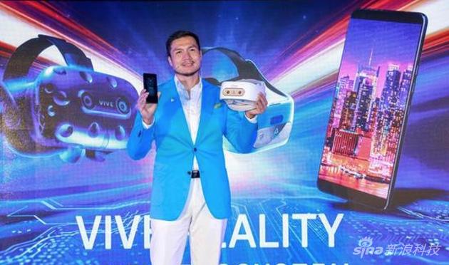 左手拿着U12+右手拿着最新的HTC VR設備的HTC中國區汪叢青