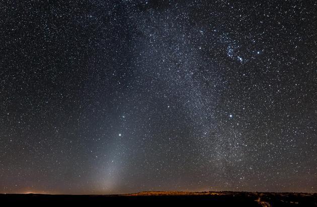 """该图像呈现的是一种被称为""""黄道光""""的现象,在图中左下方,一个发光斑块向木星方向延伸至右上方,木星中图中中心左侧的明亮天体,黄道光是由太阳系内部微小尘埃(彗星和小行星的解体残骸)反射太阳光形成的,使用哈勃太空望远镜测量太阳黑暗程度会受到周围污染光的干扰。"""