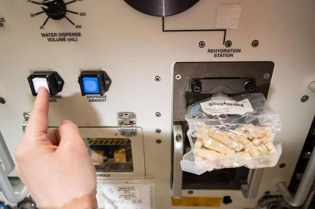 图为宇航员向经过冻干处理的食物中添加热水。