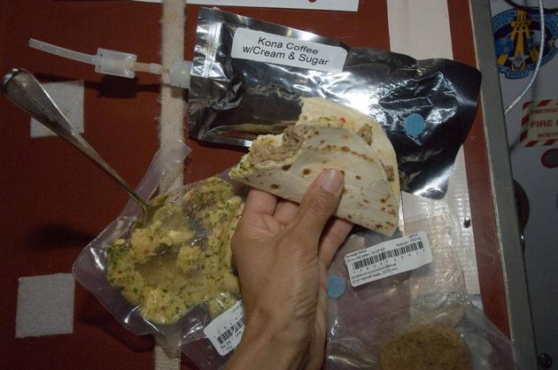 宇航员进餐时,要用维克牢尼龙搭扣将食物包装袋固定在餐桌上。由于墨西哥玉米饼不易产生碎屑,可以做成卷饼食用。