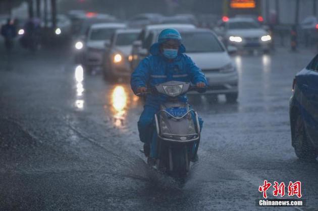 图为外卖小哥在暴雨中骑行。 骆云飞 摄