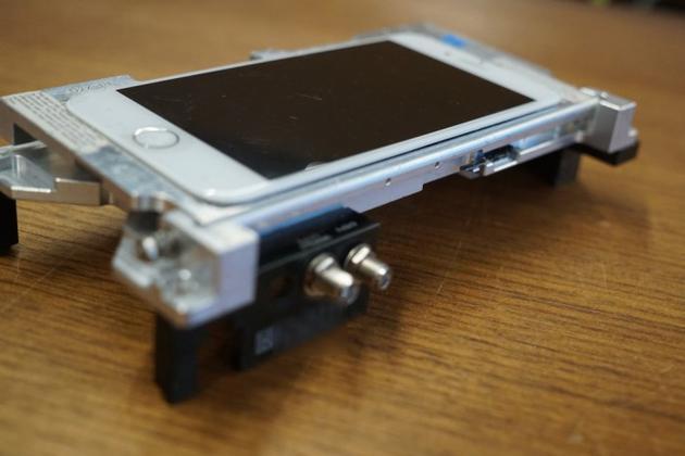 "一台安装在支架上的""dev-fused""版iPhone(Image: Motherboard)"