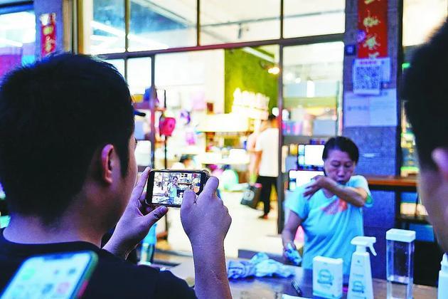 围观的拍客正在拍摄英姐表演卖货的段子。