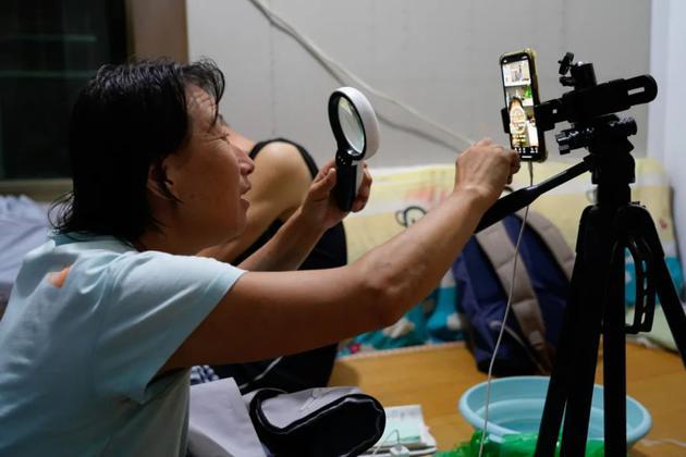 直播中,英姐拿放大镜看手机屏幕上的文字。本文照片均由中青报·中青网记者杨海/摄