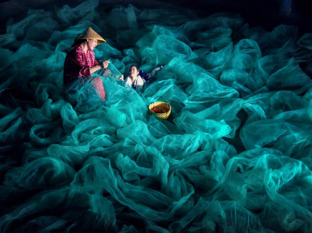 照片拍攝于福建省霞浦縣北兜村,漁民在休漁季節補網。母親與孩子仿佛在編織的,是美好的生活和希望。畫面的視覺張力和動人的細膩情緒,都揉進了這張漁網里。   ——用戶7019