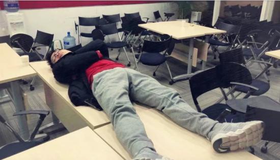 一位同学躺在桌子上睡觉,被无情偷拍