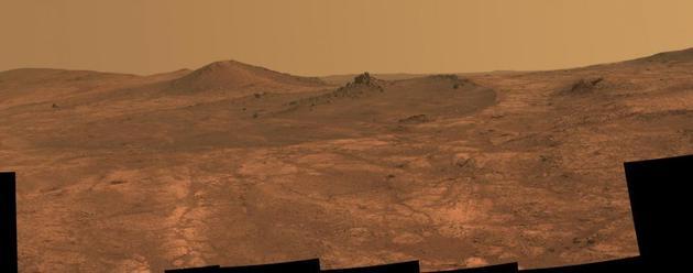 """在这张由NASA火星探测器""""机遇号""""全景摄像机拍摄的照片中,一个名?#23567;?#22307;路易斯精神?#20445;⊿pirit of St。 Louis)的陨石坑和一块尖尖的岩石占据了画面的主体。"""