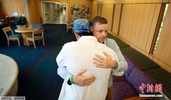 资料图:一名成功实施换脸手术的男子与医生拥抱表达感谢。