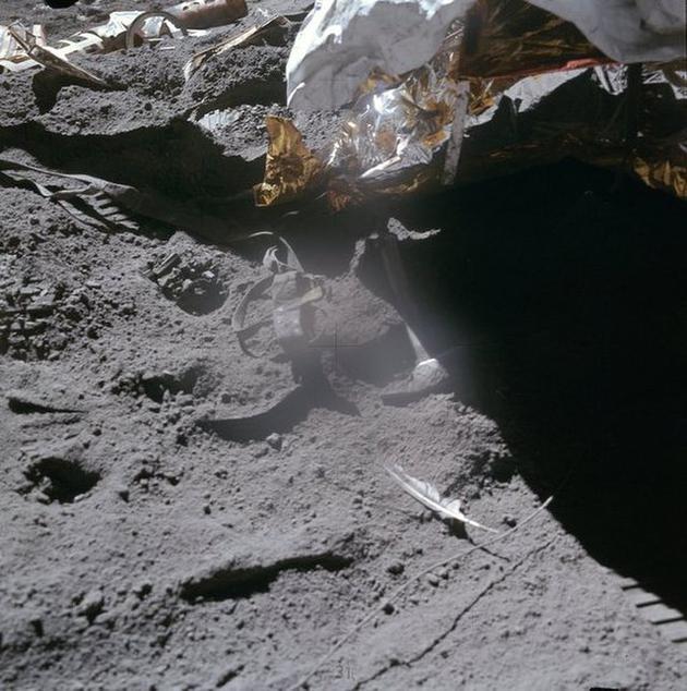 图为留在月球上的锤子和老鹰羽毛。