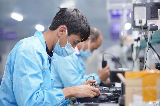数字电子示范区内企业的工人正在加工电子设备(央广网发 通讯员冯浩然 摄)