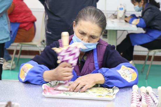 在新疆和田地区于田县夏玛勒巴格村的库尔班手工坊中,村民正在制作手摇扇(央广网记者 刘阳 摄)