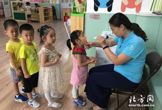 幼儿园保健医生检查幼儿咽部、手部掌侧着力部位是否有疱疹