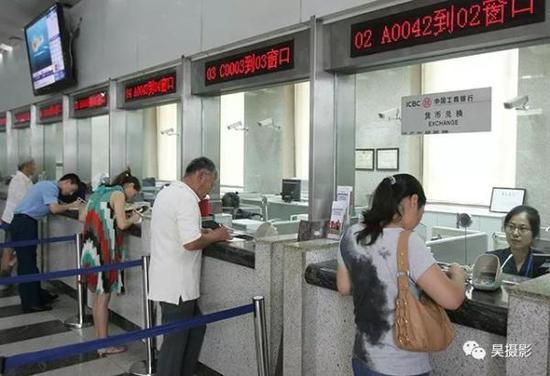 2012年7月,市民正在银行窗口办理业务。张磊摄