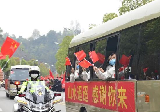 天津医疗队队员向群众挥旗示意