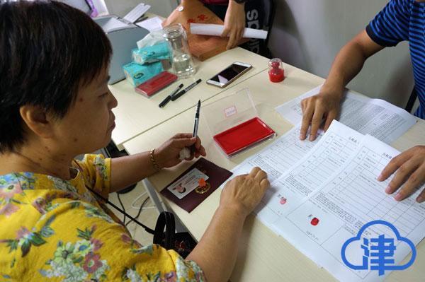 (张贵荣在选房确认书上签字、按下手印)