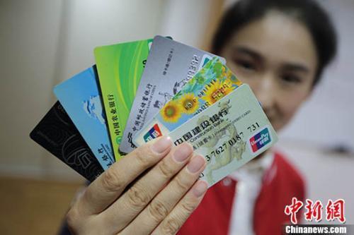 图为一位市民展示她所拥有的不同银行的银行卡。(资料照片) 中新社记者 泱波 摄