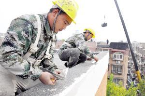 图为施工人员对楼梯外檐进行整修。