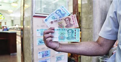 """本市一些消费者从银行取出新版人民币""""尝鲜"""""""