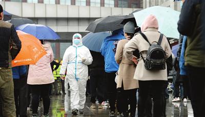 市民排起长队,在雨雪中静静地有序等待核酸检测
