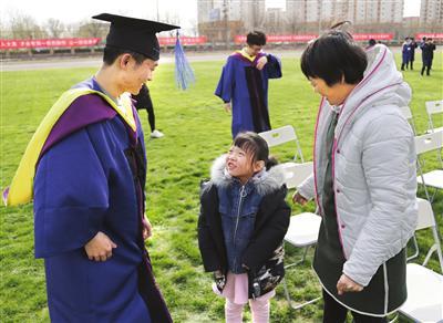 一名山东毕业生的母亲带着7岁小女儿参加大儿子的毕业礼。