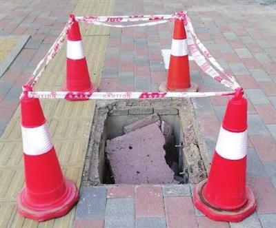 """河西区九江路上的""""病害井""""被工作人员用锥形桶围住。"""