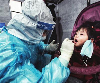 小女孩很懂事地配合医护人员检测 本报记者 吴迪 张磊 刘玉祥 王涛 摄