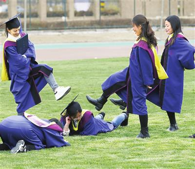 毕业生在草地上?#29420;?#30041;影。