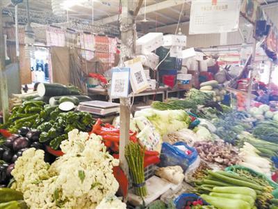 如今很多蔬菜商户都挂着二维码收款标志。