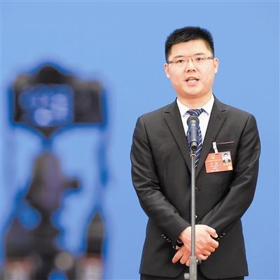 """5月25日,李君在""""代表通道""""通过网络视频方式接受采访。 新华社记者 李贺摄"""