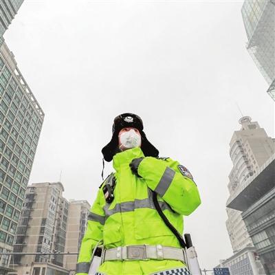 """2月14日,我市迎来降雪,河东区新开路上值守的交警在风雪中站""""疫""""。"""