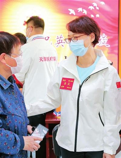 图为张岚(右)与社区党员交流心得。