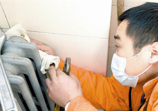 维修工作人员在卫生间内更换老旧的暖气阀门