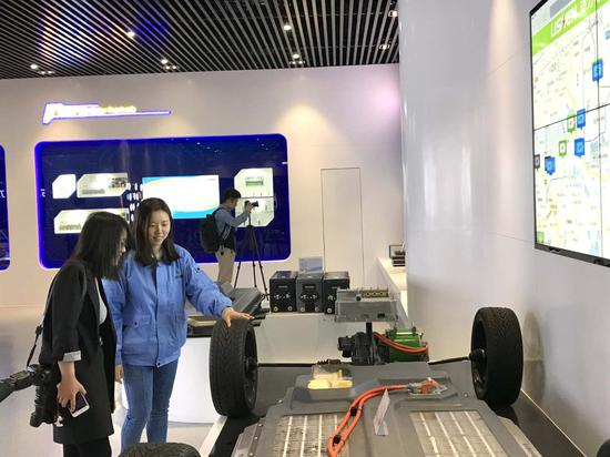 讲解员为记者讲解电动汽车电池系统